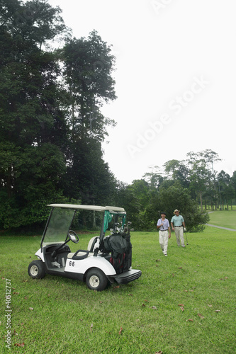 Two men walking towards golf cart