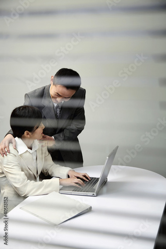 Businessman putting his hands on businesswoman's shoulders