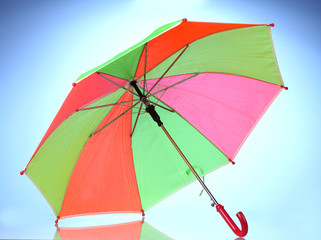 Multi-colored umbrella on blue background