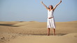 Woman with wide open arms standing on the desert
