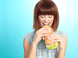 beautiful young woman eating a big sandwich