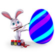 Easter bunny painting a egg with blue