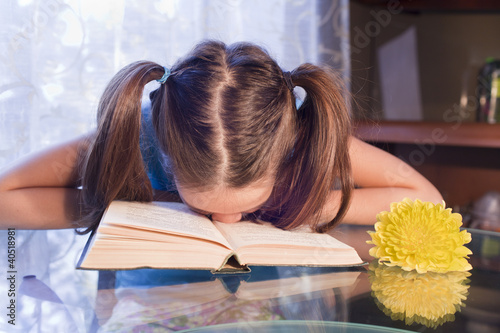 school girl puts down her head at the book