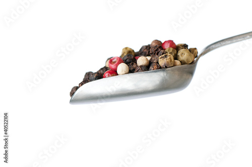 silver spoon with pepper on white background
