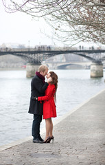 Romantic couple in love kissing near Pont des Arts in Paris