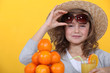 Little girl with pile of oranges wearing straw hat