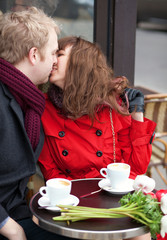 Happy couple kissing in Parisian cafe