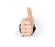 Thumbs up through the paper hole isolated on white background