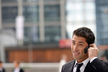 Yuppie businessman making a call outside office