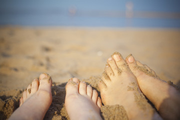 happy grils feet and warm sand of the beach