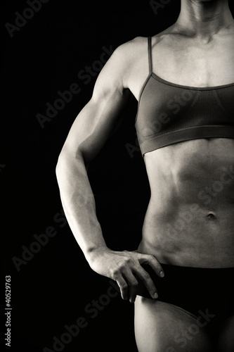 Female bodybuilder posing against black background