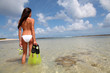 Back view of woman holding snorkeling accessories by the sea