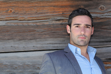 Portrait of businessman standing in front of wooden wall