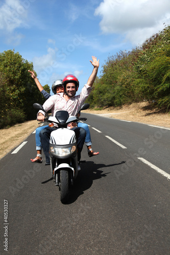 Couple enjoying scooter ride on country road