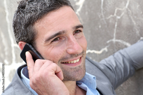 Businessman talking on mobile phone against wall