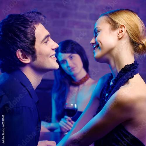 Young couple and woman looking at them at club