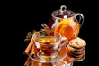 Glass teapot and cup with black fruit tea and cookies isolated