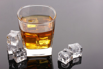 glass of scotch whiskey and ice on grey table
