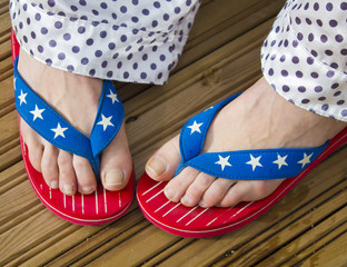 legs in flag patterned flip flop shoes
