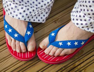 legs in flag patterned flip flop shoes