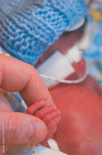 A premature baby holds his father's finger