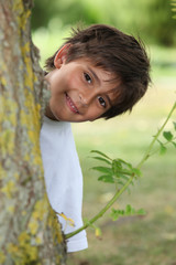 Boy behind tree trunk