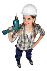 A female construction worker holding a drill.
