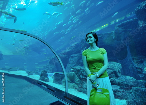 young woman with big aquarium in backgrond