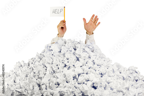 Person under crumpled pile of papers with hand holding a help si