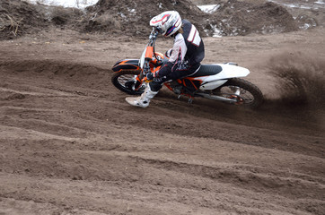 Motocross rider veering point-blank of sand with