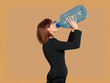 attractive, young businesswoman drinking water, big bottle