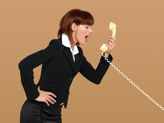 attractive, young businesswoman screaming into the telephone