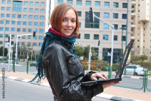 A woman and her laptop at the city