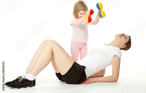 Young mother and her little daughter doing sport exercises