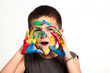 bambino con colori sulla faccia e le mani