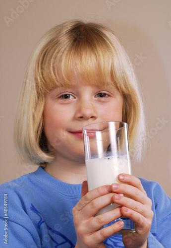 Niña bebiendo un vaso de leche.