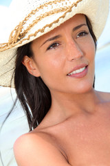Closeup of attractive woman wearing hat at the beach