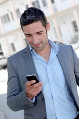 Businessman using mobilephone out in town