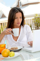 Beautiful woman connected on internet while having breakfast