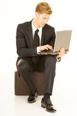 businessman with laptop sitting on a suitcase