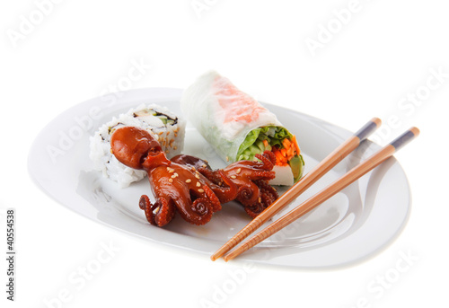 Baby octopus, sushi and spring roll on a plate