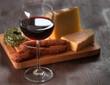 Wein und Käse auf dunklem Holz
