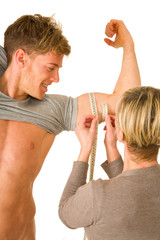 woman measuring biceps of a young man