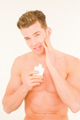 Young man applying aftershave