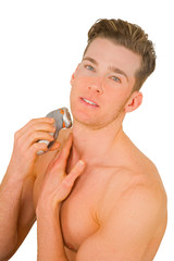 Young man shaves with electric razor