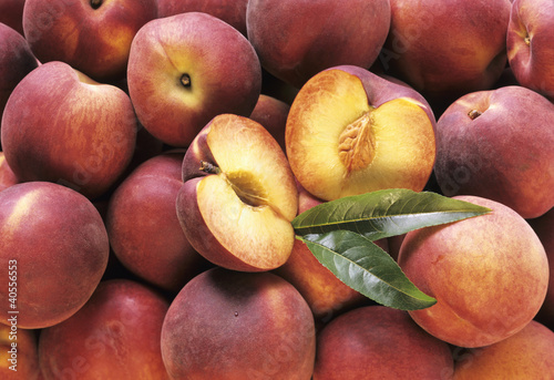 Many Whole Peaches with One Halved (Full Frame)