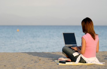 Woman Working at Computer on the Beach