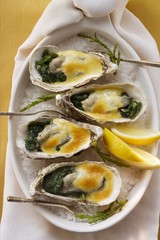 Baked oysters with creamed cheese and spinach on sea salt