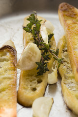 Slices of toasted white bread with garlic and thyme