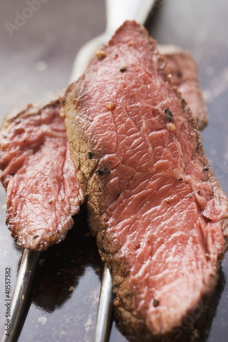 Two slices of beef steak on meat fork